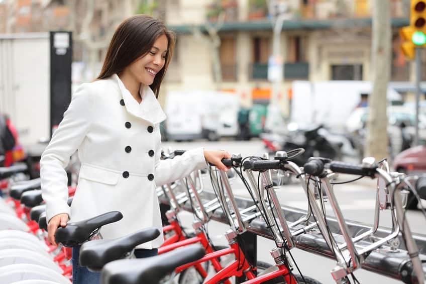 Imagem de uma mulher sorrindo colocando bicicleta no bicicletário.