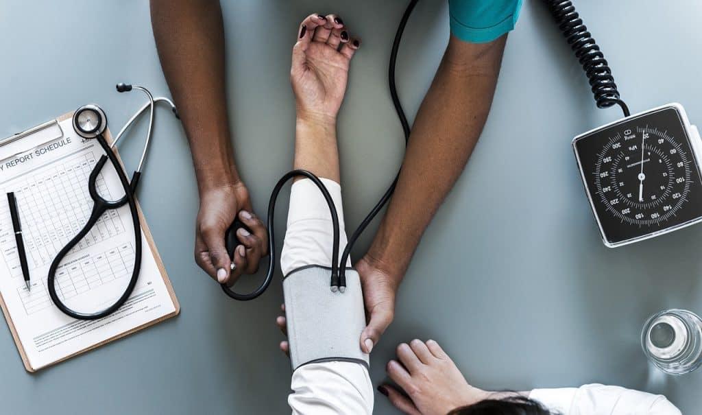 A foto mostra visão de cima de uma mesa. Uma pessoa está com o braço esticado com um manguito em volta dele e outra, aparentemente um profissional da saúde, está medindo sua pressão.