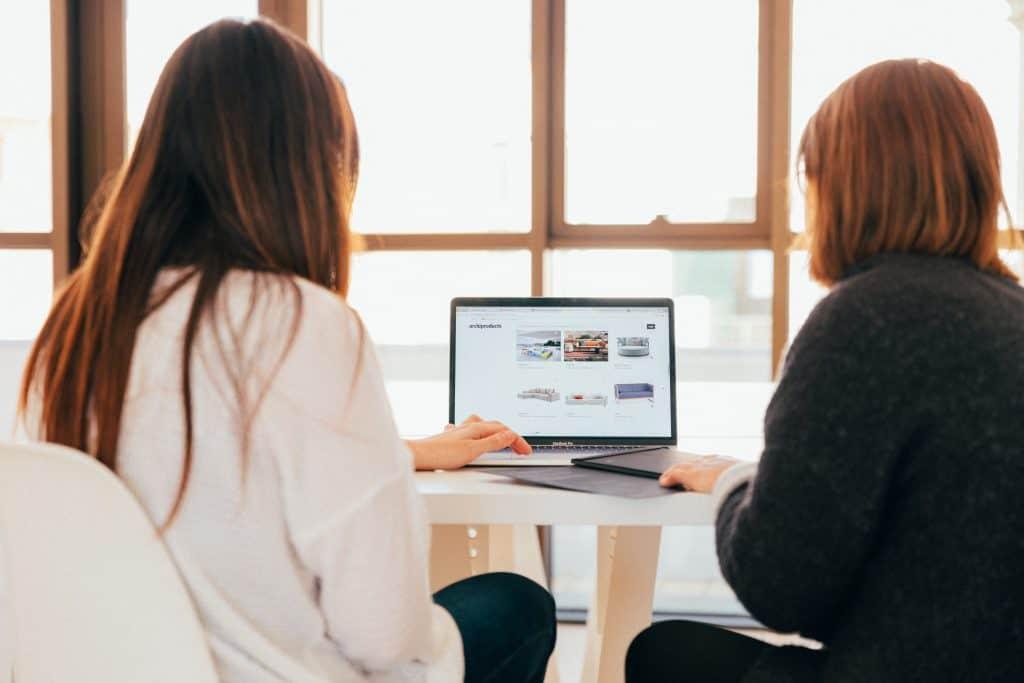 Imagem mostra duas mulheres em frente a um laptop.