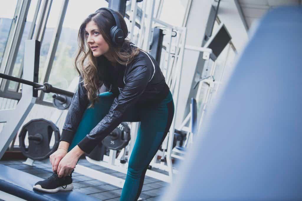 Mulher na academia de ginástica com fone de ouvido.