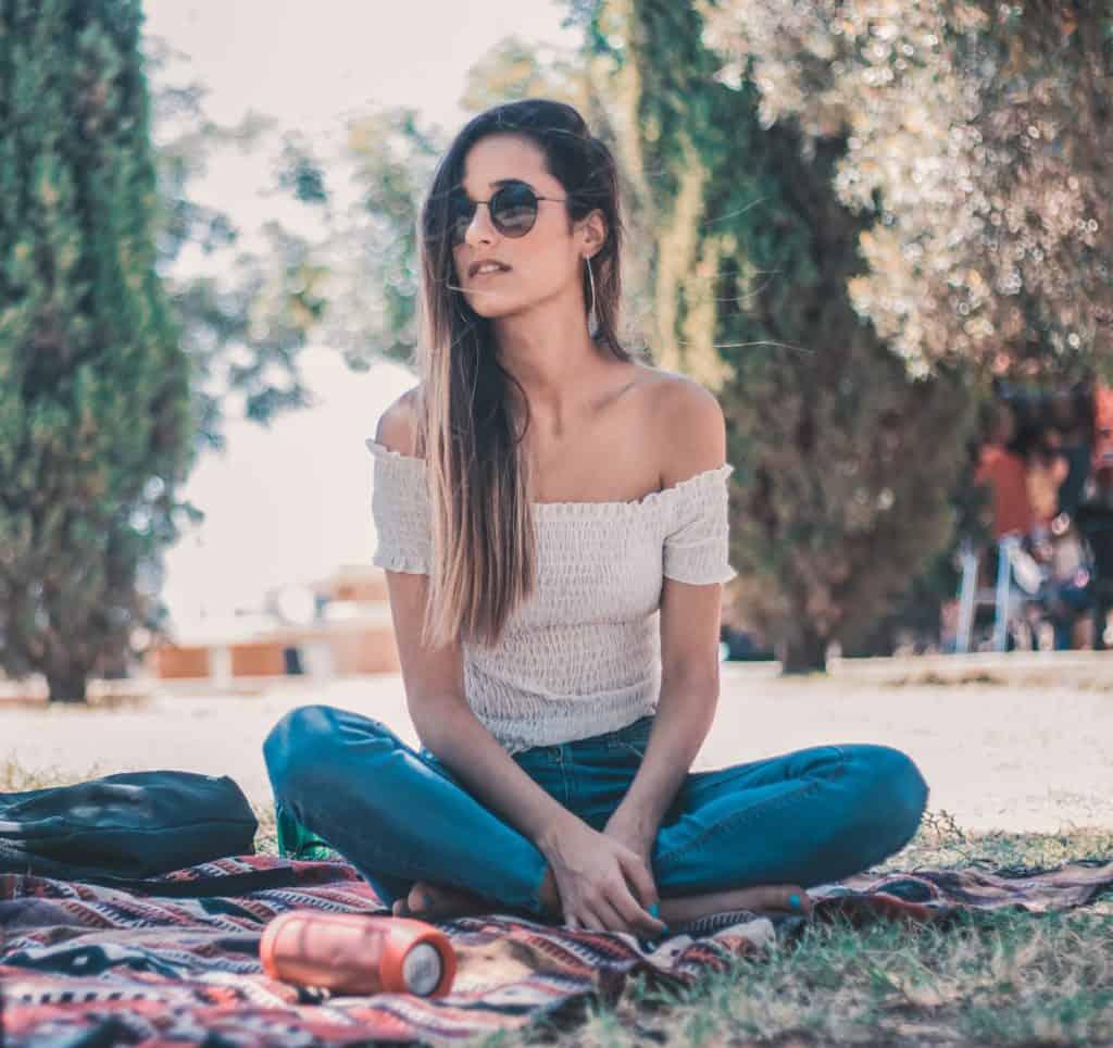 Imagem de uma moça escutando música em um parque com uma caixa de som JBL.