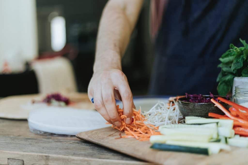Imagem mostra um homem colocando legumes cortados em uma tábua de madeira.