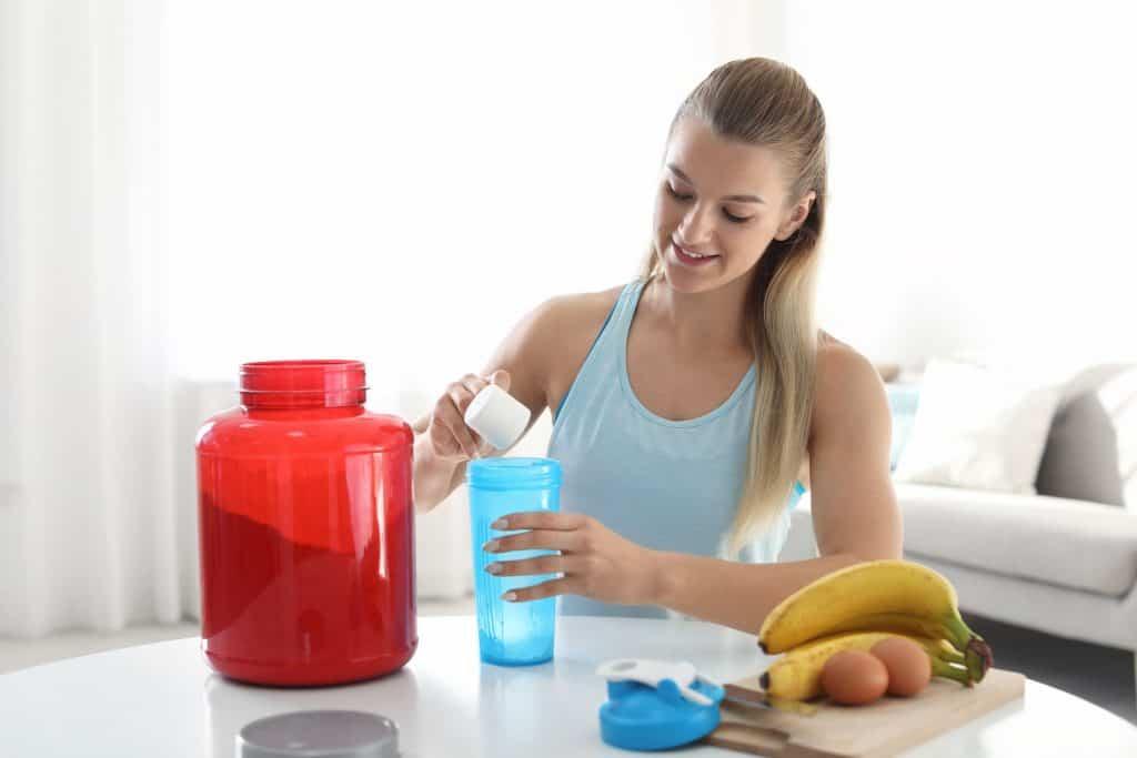Mulher preparando bebida com Whey Protein.