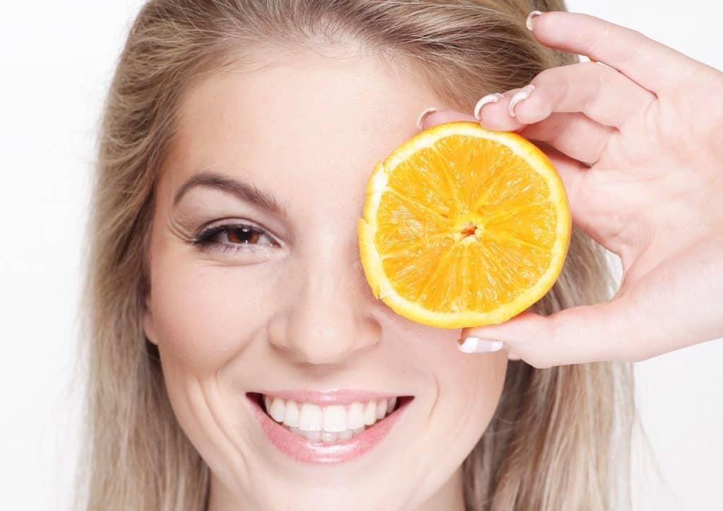 imagem de uma mulher com uma rodela de laranja em frente ao rosto
