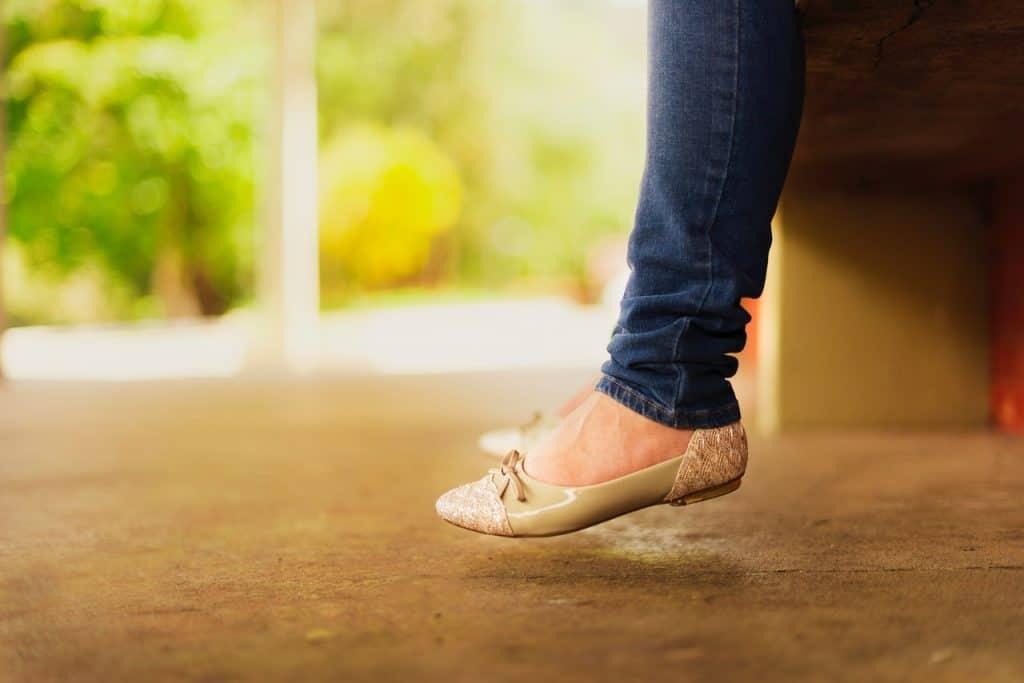 Na foto estão as pernas de uma mulher sentada com calça jeans e sapatilha bege.
