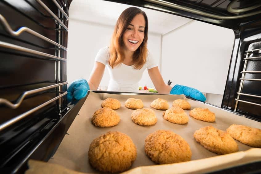 Imagem de dentro do forno de mulher retirando cookies e sorrindo.
