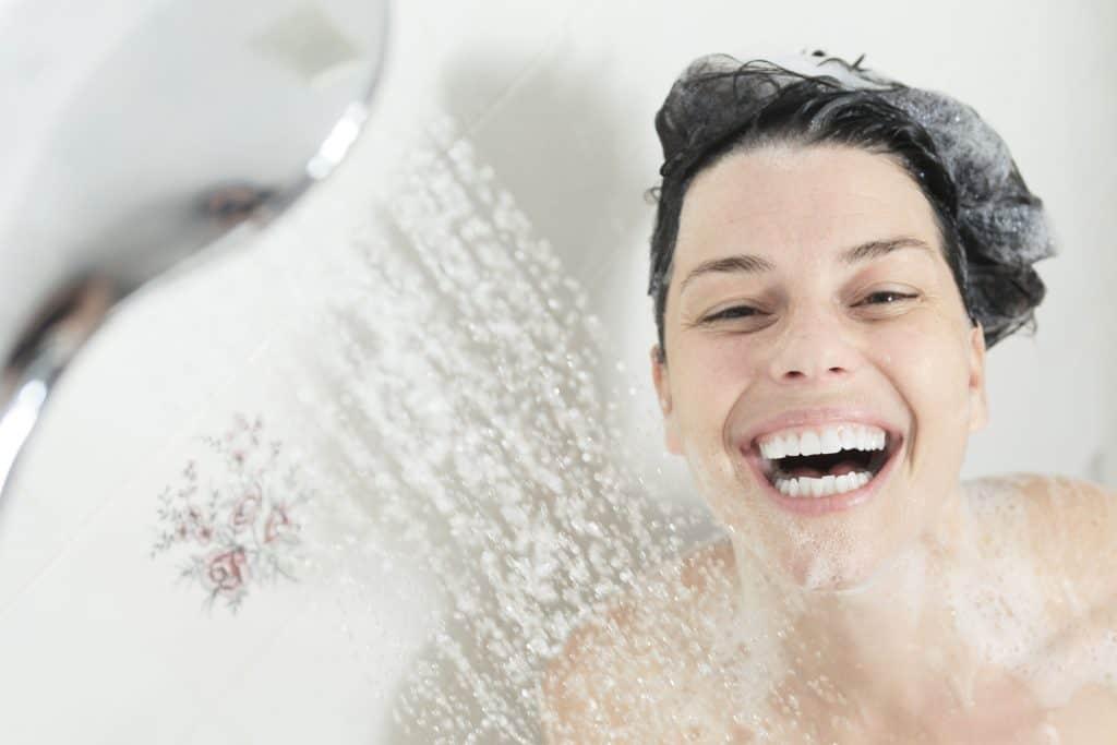 Imagem de uma mulher feliz tomando banho de chuveiro.