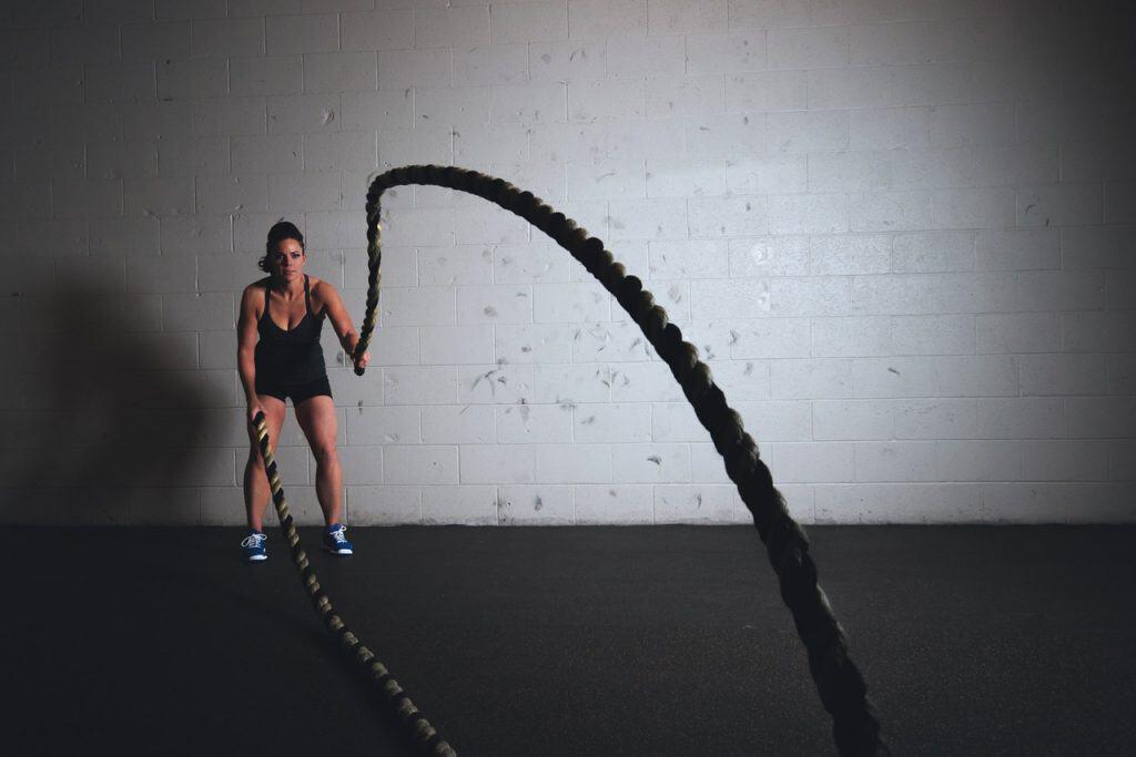 Imagem mostra uma mulher se exercitando com cordas, em frente à uma parede branca e sob um piso escuro.