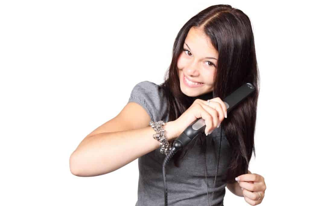 Imagem de mulher de cabelos longos utilizando uma chapinha para modelar os fios.