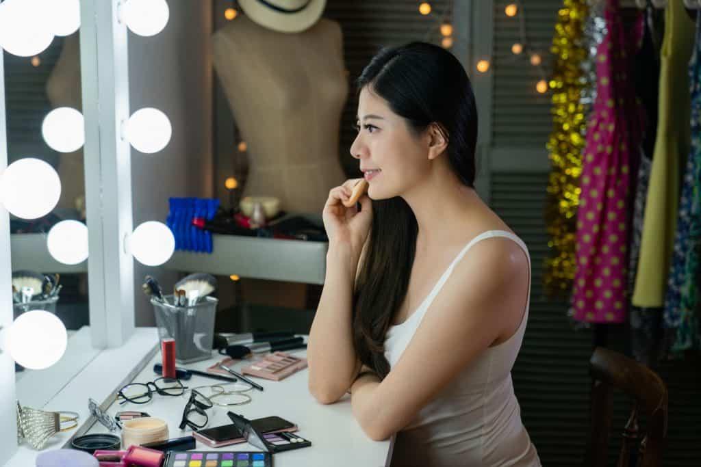 Imagem de mulher fazendo maquiagem em espelho de penteadeira.