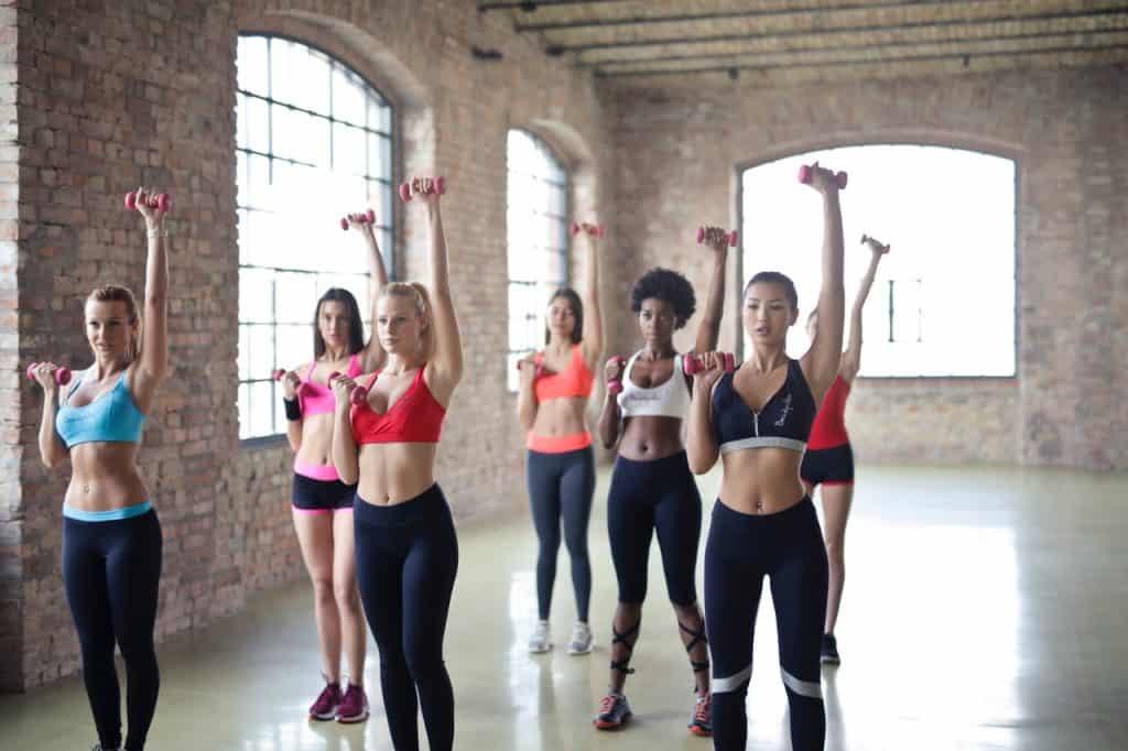 Imagem mostra sete mulheres agrupadas, levantando pesos no dois braços. Os esquerdos, estão levantados e esticados, os direitos, formando ganchos, com as mão na altura dos peitos.