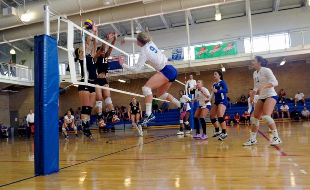 Jogo de vôlei feminino. Há algumas pessoas na arquibancada e jogadoras na quadra. Três delas estão dando um salto na direção da rede.