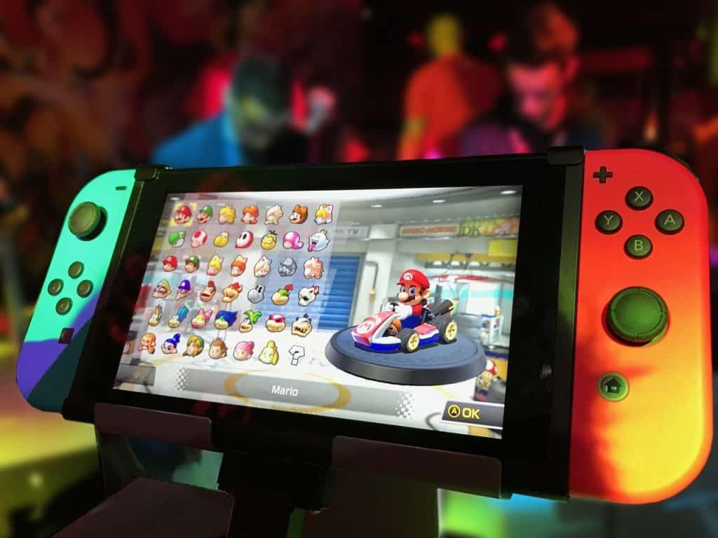 Um Nintendo Switch reproduzindo na tela o jogo Mário Kart Deluxe.