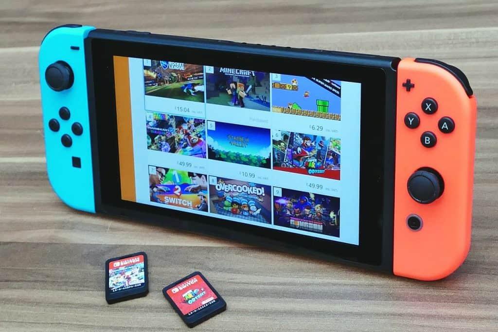 Um Nintendo Switch apoiado em uma mesa e dois cartuchos de games.