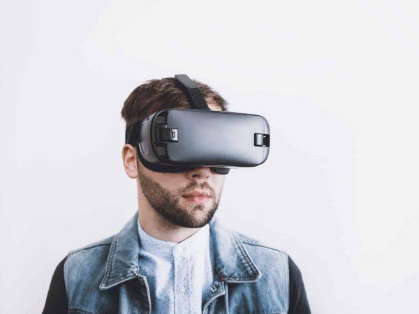 Homem jovem usando óculos virtual em fundo branco.