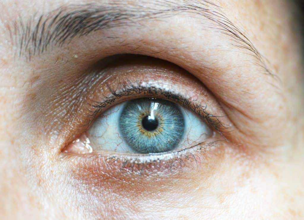 Foto de um olho azul, com um pouco de olheira ao redor.