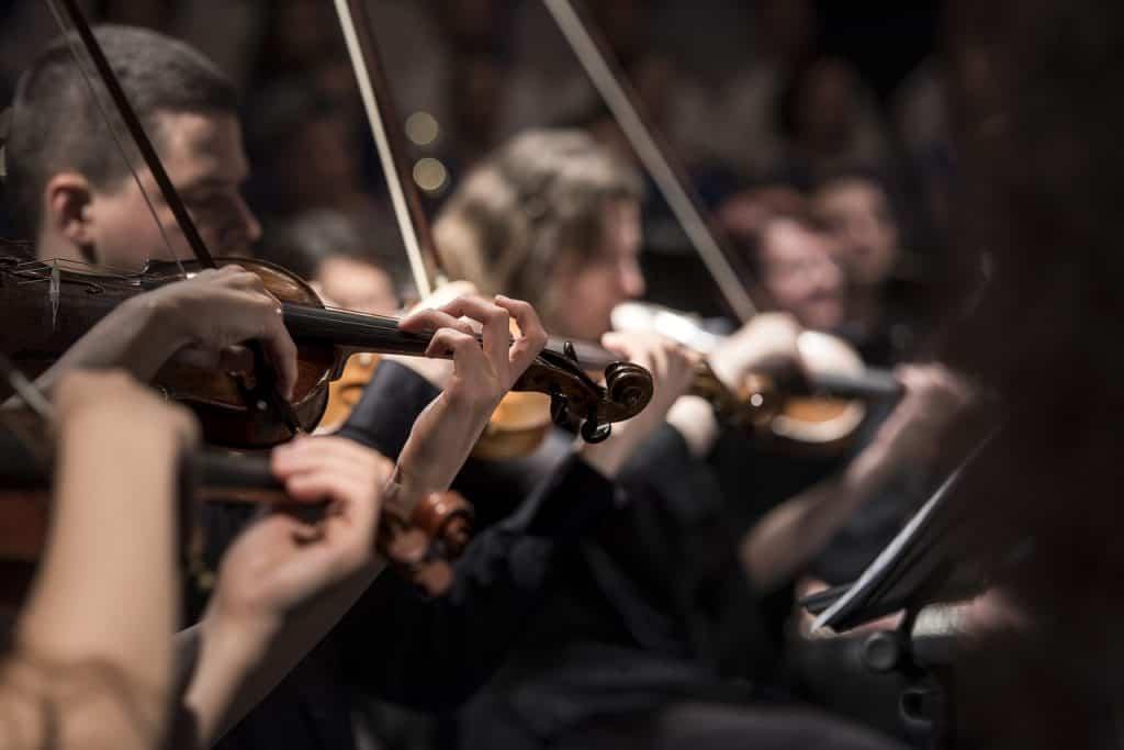 Foto em close de uma orquestra, mostrando uma linha de violinos onde todos possuem o instrumento e o estão tocando.