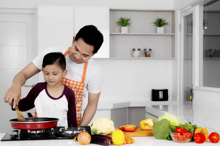 Pai e filho cozinhando em fogão e legumes ao lado.