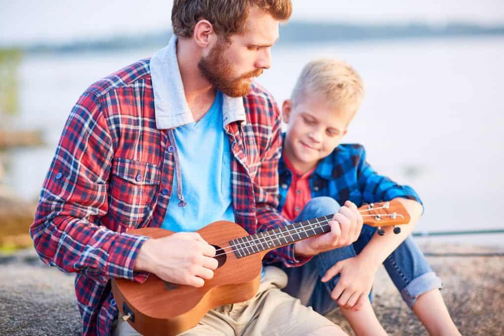 Imagem de pai e filho tocando ukulele sentados.