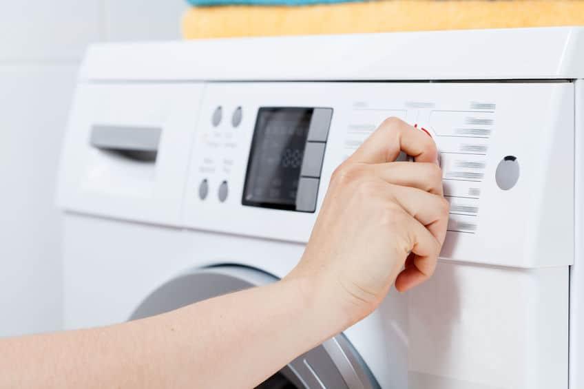 Imagem de painel de máquina de lavar e pessoa mexendo.