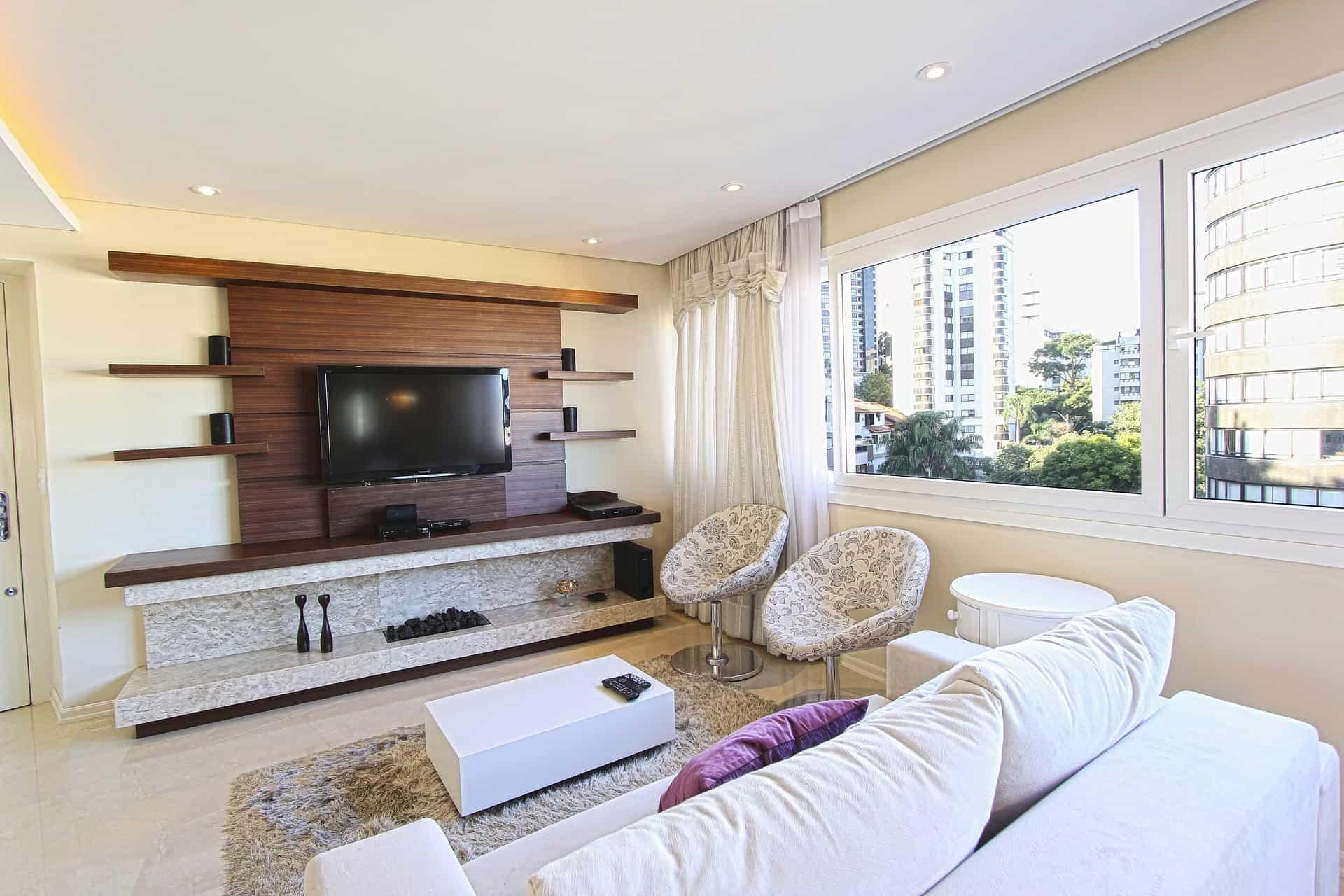 Sala de estar bem iluminada, com móveis claros e painel para tv.