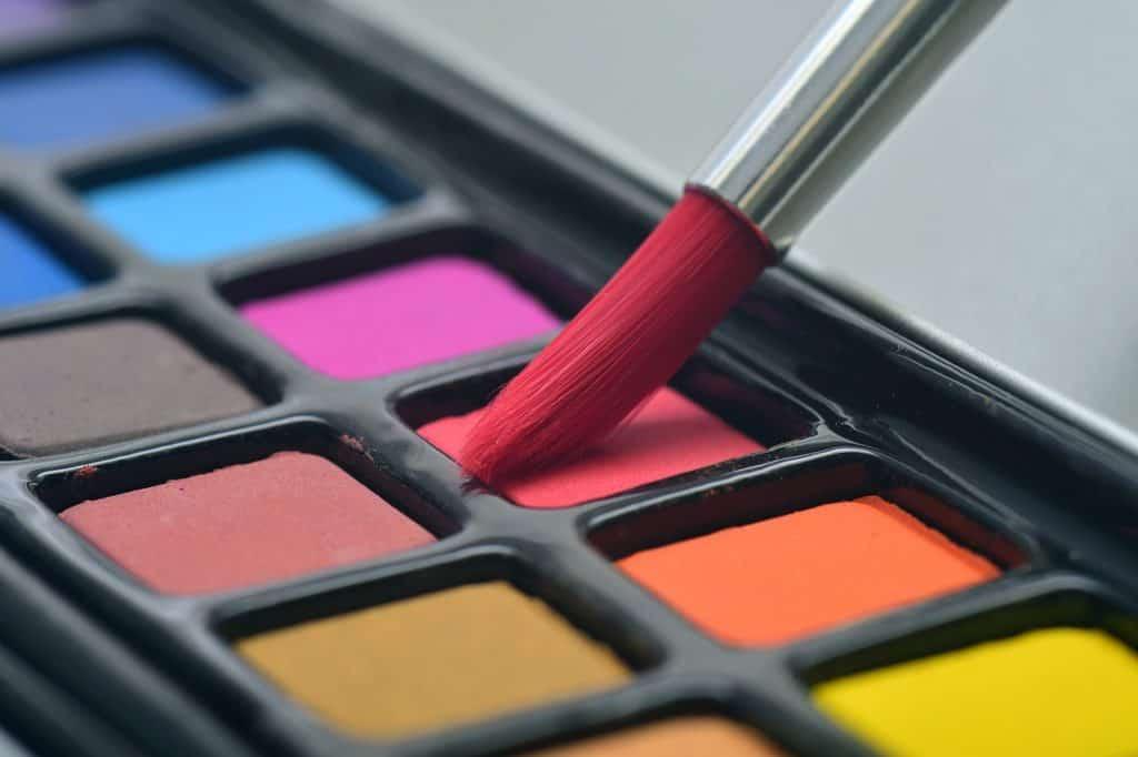 Na foto um pincel sendo colocado em cima de uma paleta de tintas.
