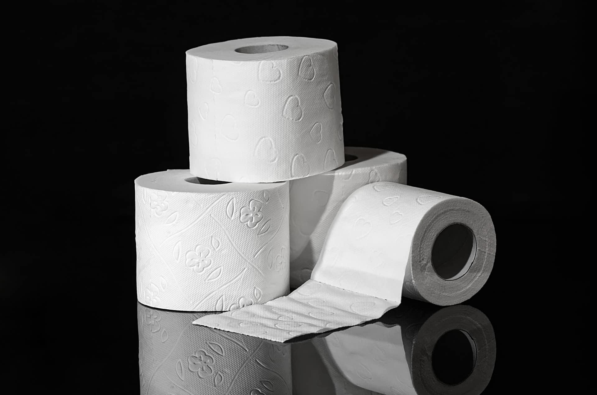 Imagem três rolos de papel higiênico sobre bancada preta em fundo preto.