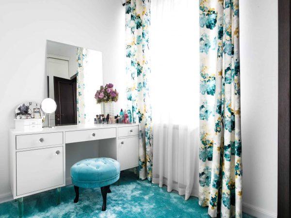 Foto de penteadeira branca, com espelho e produtos de beleza em cima. Banco verde na frente.