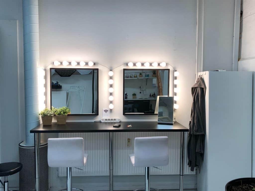 Imagem de penteadeira camarim com luzes ligadas.