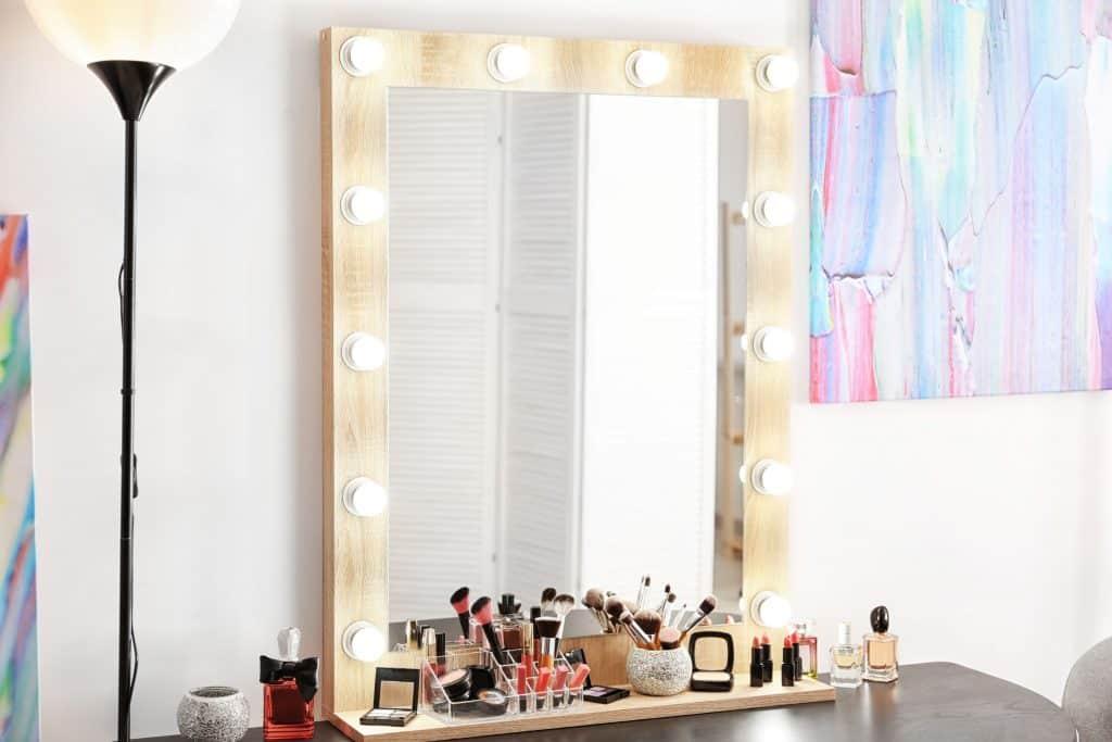 Imagem de penteadeira com maquiagem em cima e luzes em volta.