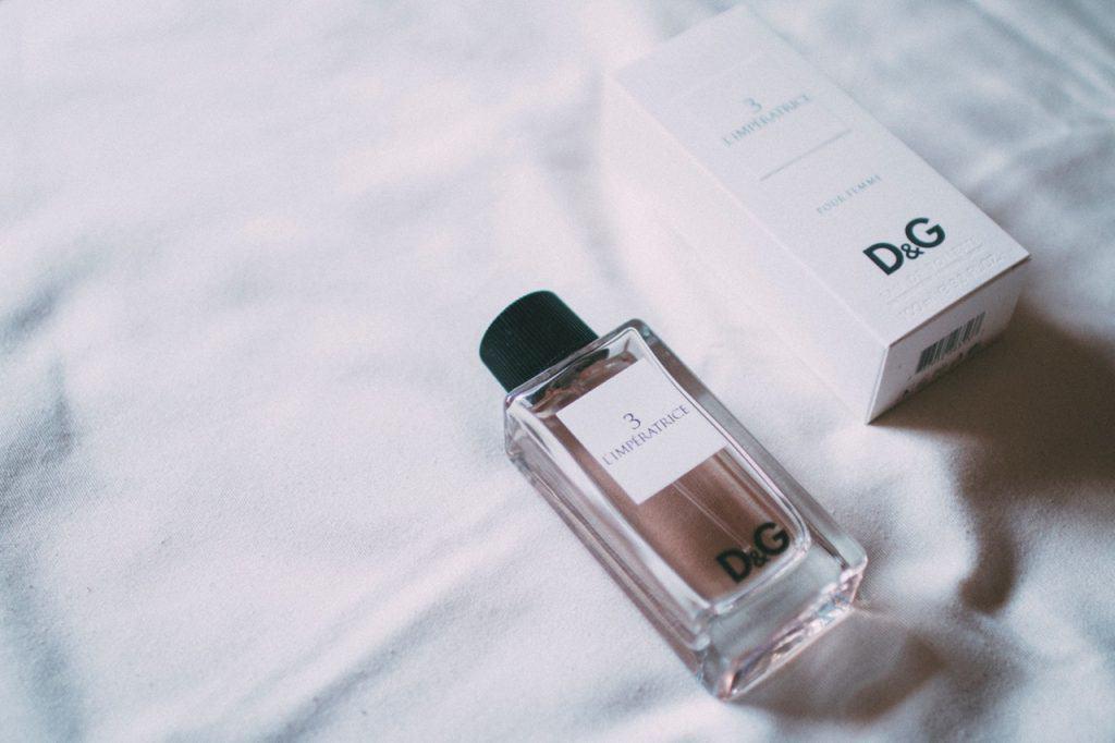 Foto de um frasco de perfume da marca Dolce & Gabanna, ao lado de uma embalagem do mesmo perfume. Ambos estão em cima de uma cama, com lençol branco.