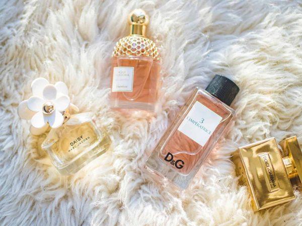 Foto de quatro vidros de perfume femininos, em cima de algo que parece um tapete ou manta de pelinhos brancos.