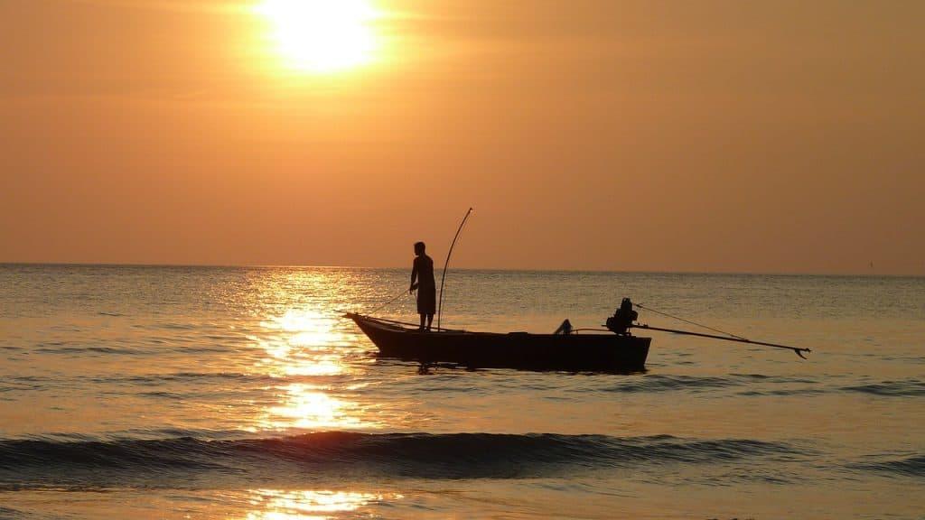 Imagem de dois pescadores com vara de pesca em barco pequeno no mar com sol ao fundo.