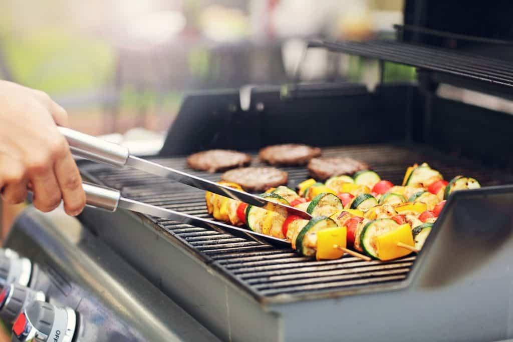 Imagem de pessoa assando carne e legumes em churrasqueira a gás.