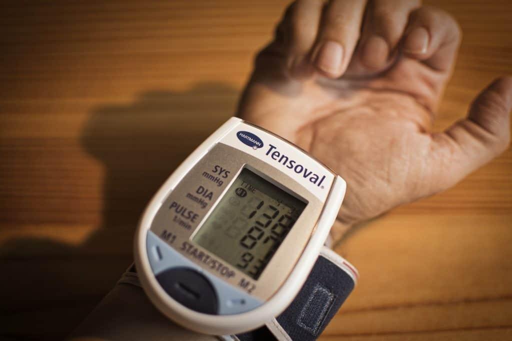 Mão e braço com um medidor de pressão no pulso.