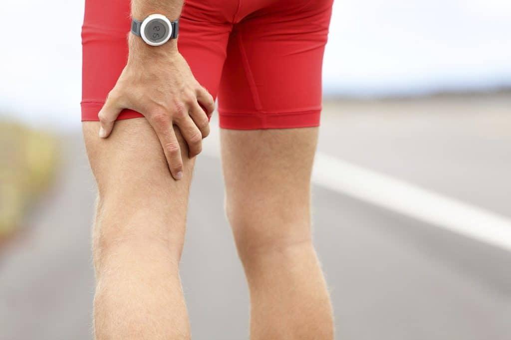 Imagem de uma pessoa com a mão na parte posterior da coxa, sugerindo dor.