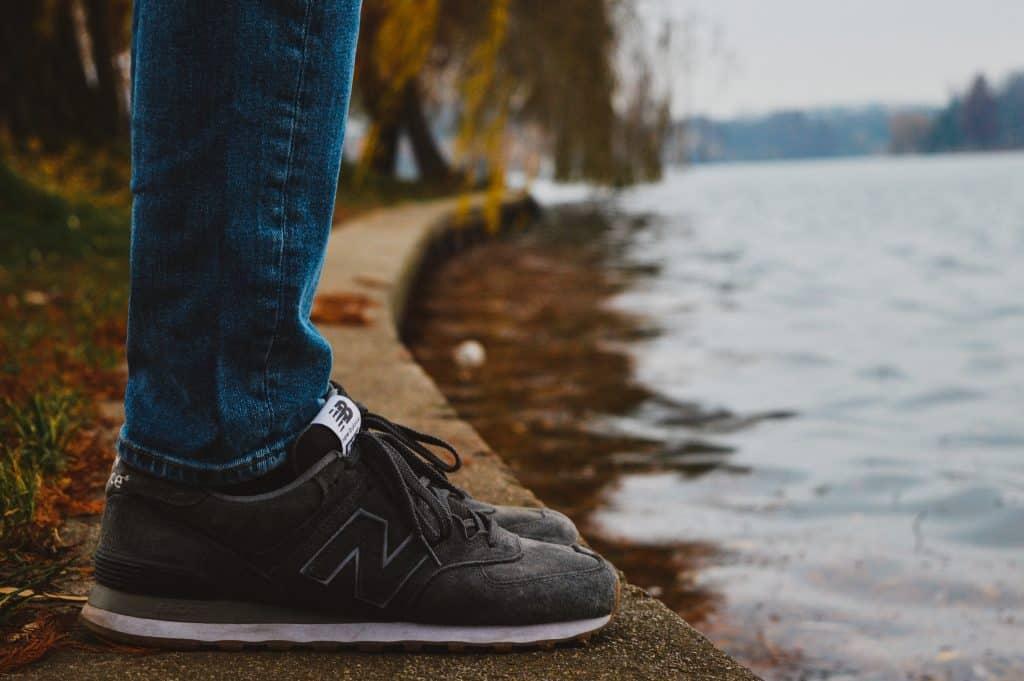 Imagem de pessoa em frente a um lago usando um new balance.