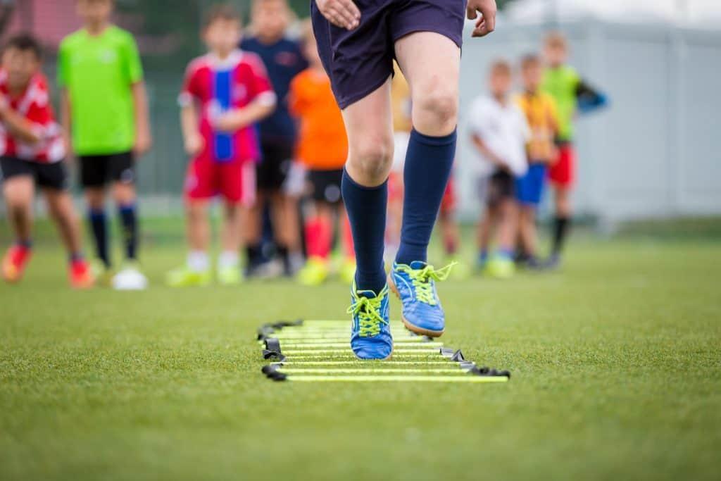 Garoto passando sobre a escada de agilidade estendida no gramado em um treino de futebol.