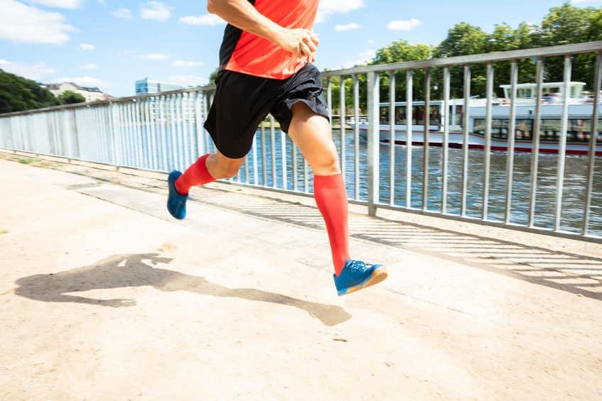 Imagem de pessoa correndo na beira de lago e utilizando meia de compressão.