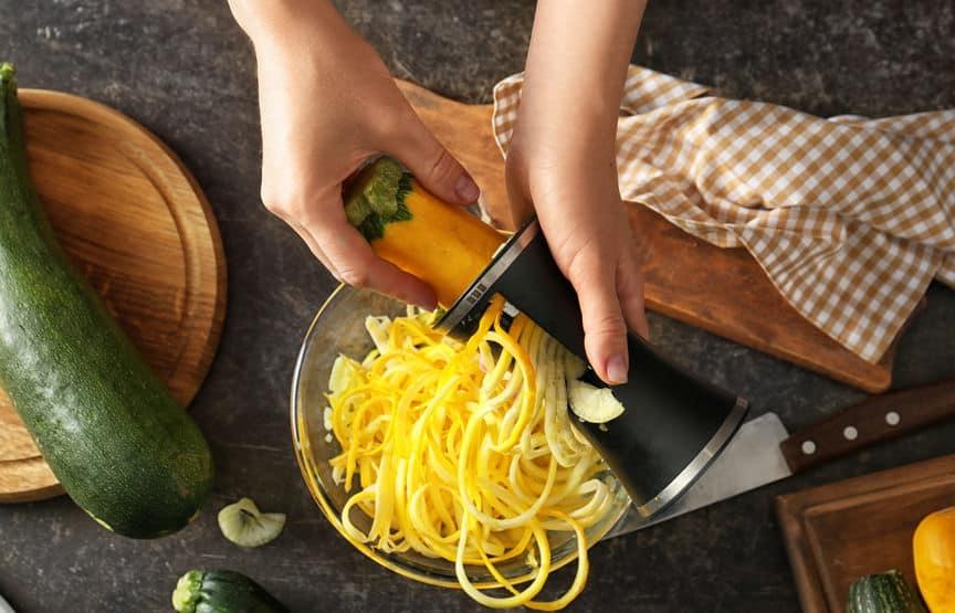 Mão de mulher fatiando abobrinha no fatiador de legumes.