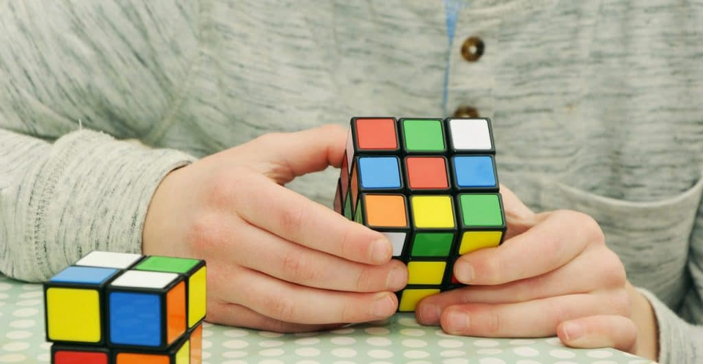 Imagem mostra mãos de rapaz montando um cubo tradicional com um cubo 2x2x2 ao lado.
