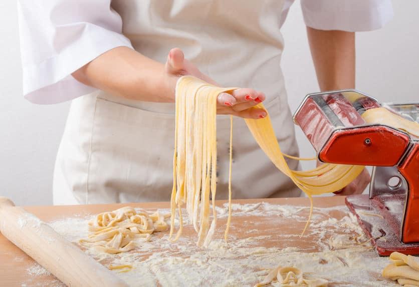 Mão segurando o macarrão saindo da máquina de macarrão.