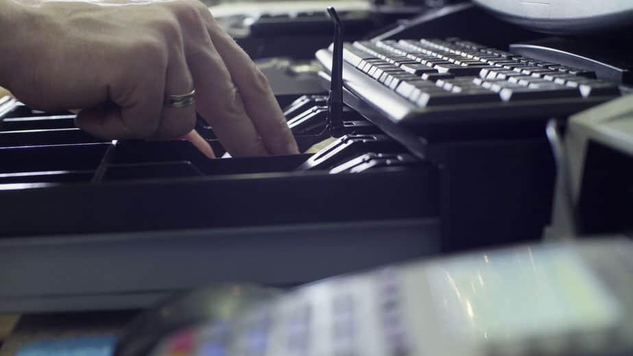 Imagem mostra a mão de uma pessoa mexendo em uma gaveta de dinheiro.
