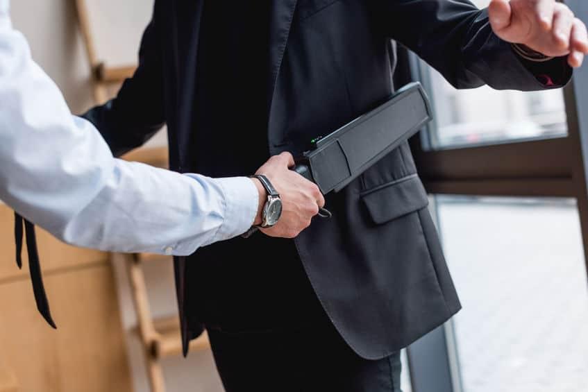 Imagem de uma pessoa passando detector de metais portátil em pessoa.