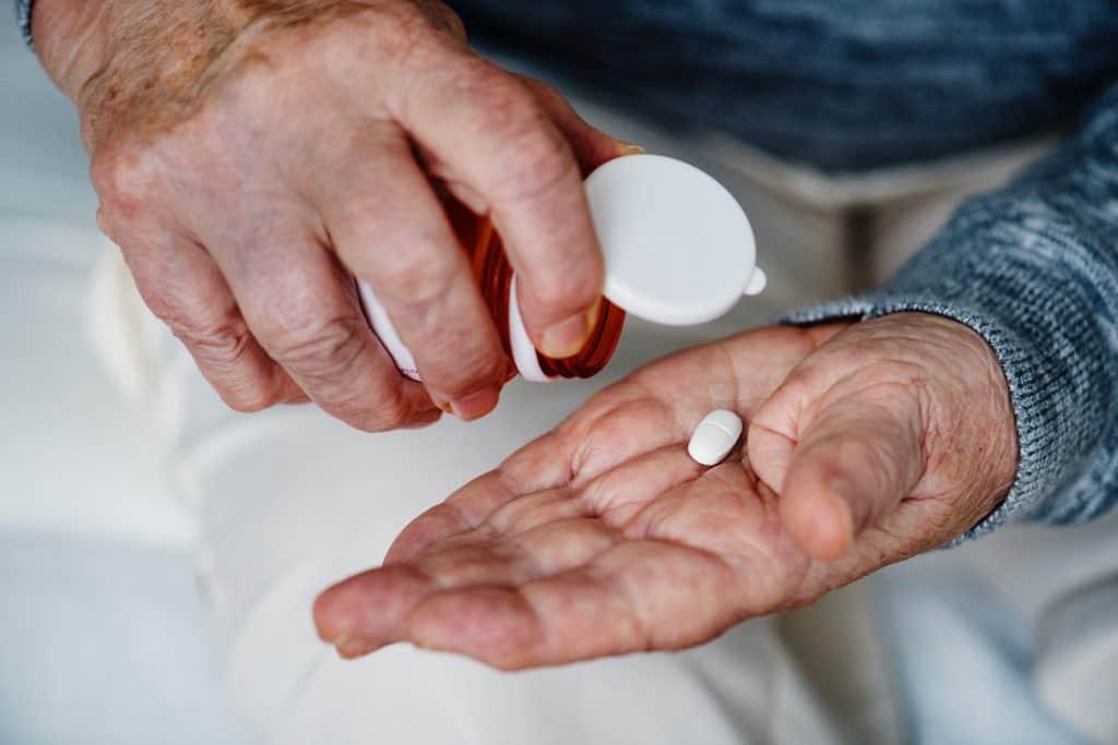 Imagem mostra um idoso separando uma pílula para consumo. Ele usa a sua mão direita para tombar o frasco, e na mão esquerda repousa a pílula.