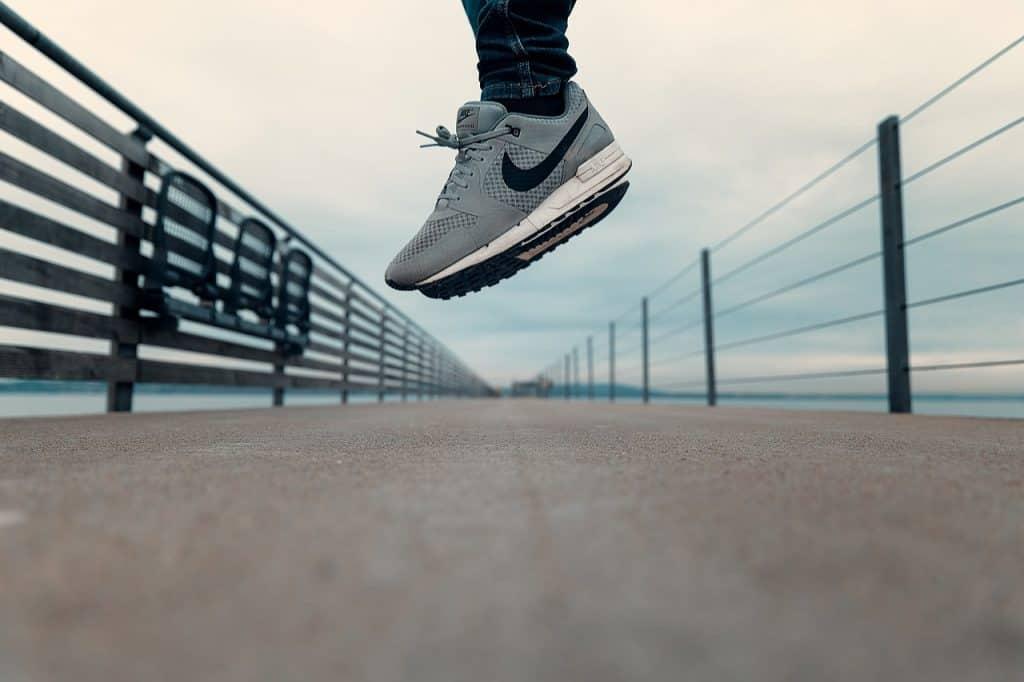 A imagem mostra um par de tênis ao alto, indicando que a pessoa pulou. Ela está em cima de uma ponte sobre o que parece um mar ou rio.