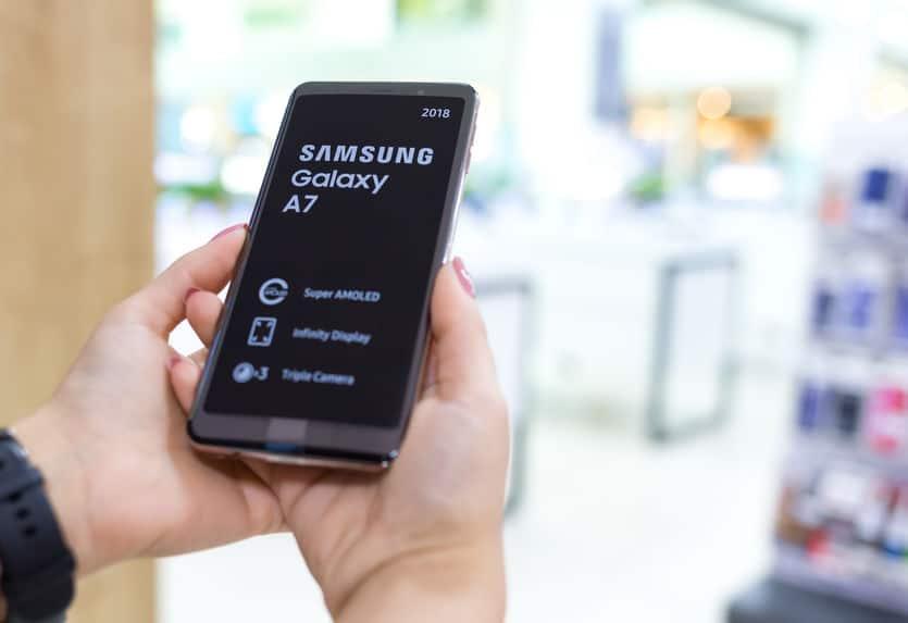 Imagem mostra um celular Samsung Galaxy A7 sendo segurado nas mãos de uma pessoa.