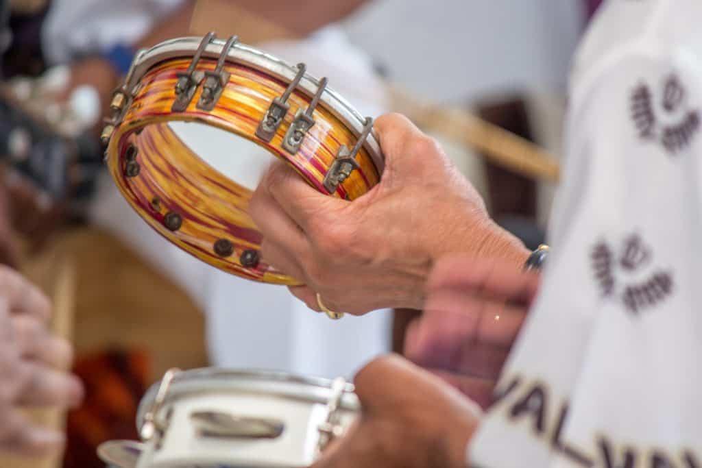 Imagem de um homem tocando tamborim em uma roda de samba.
