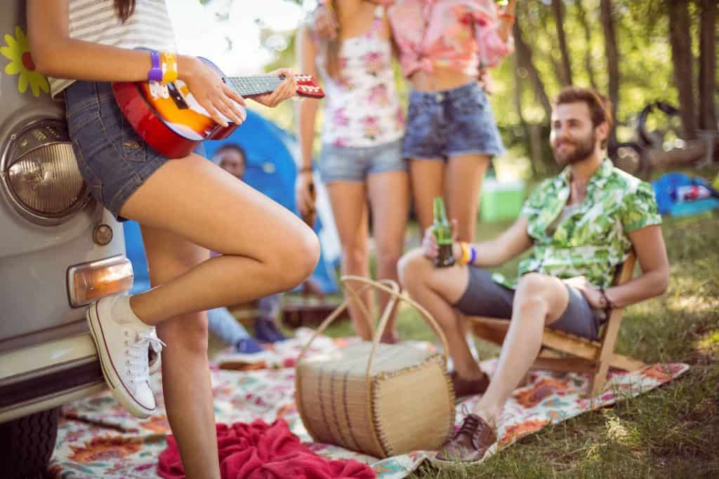 Garota apoiada em uma combi tocando ukulele entre amigos em um acampamento.
