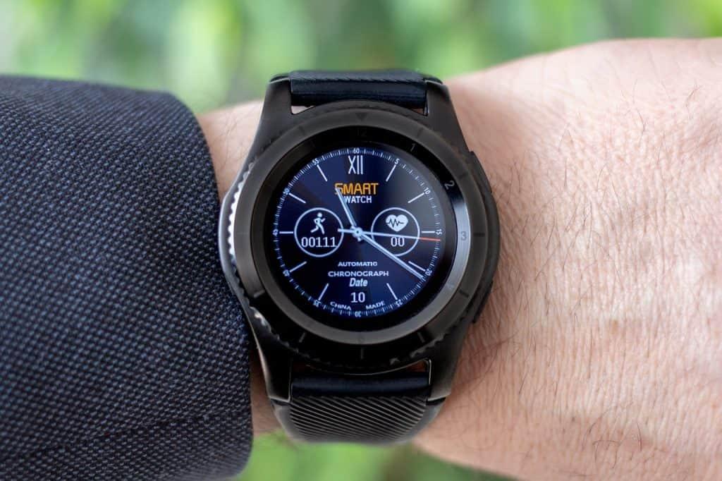 Imagem de relógio com GPS medindo passos percorridos em pulso de homem com terno.